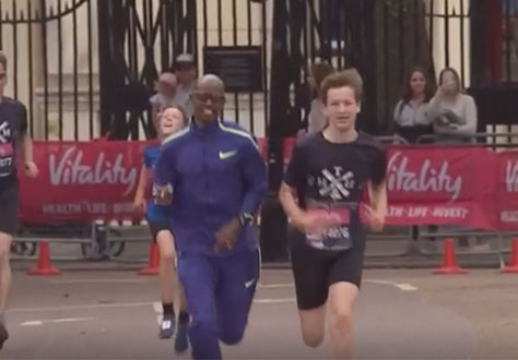 Sir Mo Farah runs alongside pupil